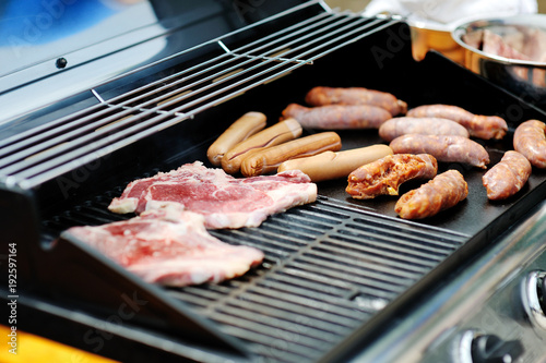 Papiers peints Steakhouse Delicious and tasty sausages and steaks cooking on a barbecue grill