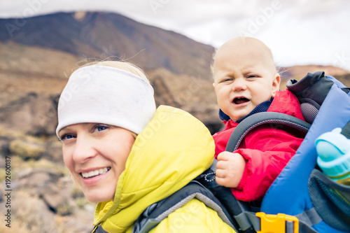 Super mother hiking with baby travelling in backpack