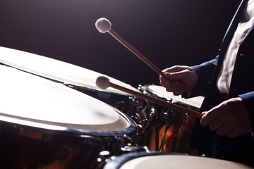 The hands of a musician playing on a timpani closeup in dark tones