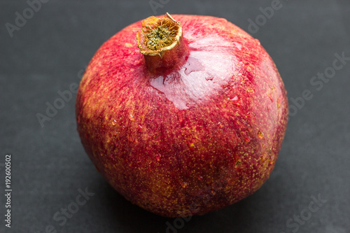 Foto Murales One whole pomegranate fruit isolated on wood background