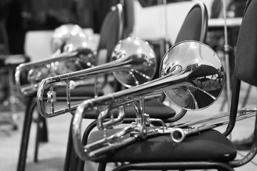 Trombones lying on chairs in black and white tones