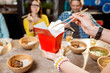 Holding a box with asian food indoors with table full of food on the background