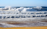 North beach of Nazare in Portugal. December. Storm.  A man on a hydrocycle evacuates a surfer from the waves of the Atlantic Ocean.  - 192610706