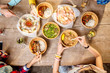 Top view on the table full of different asian meals served in the wooden plates and young people eating with sticks - 192611798