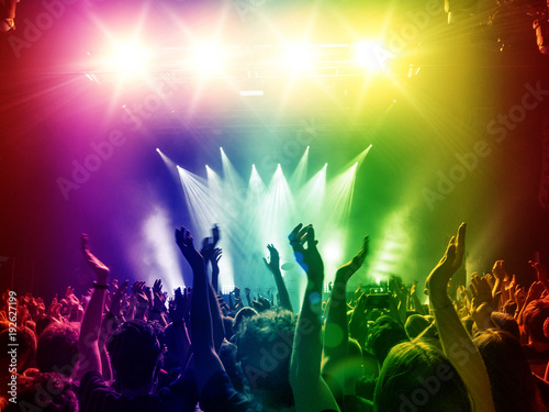 Rainbow coloured concert lights with people clapping