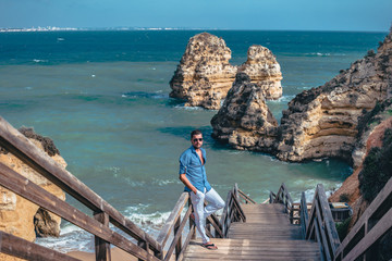 young man on vacation at the Algarve with cliffs and rocks on the beach