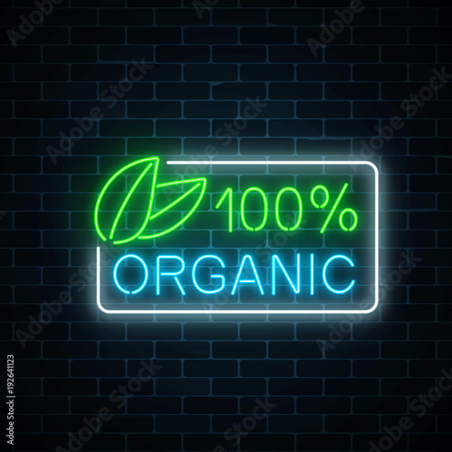 Neon 100 percent organic production sign on dark brick wall background. Natural cosmetics glowing advertising symbol.
