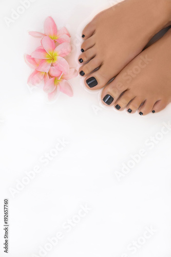 Foto op Canvas Pedicure ступни ног с черным педекюром в белой ванне с розовым цветком жасмина