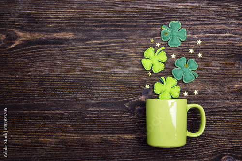Green mug with four-leaf clover on wooden background. Copy space.