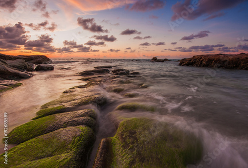 rocks covered by green moss and thick clouds during sunset.