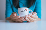 Woman hand holding a cup of coffee,close up