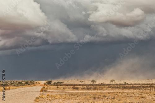 sand storm in namibia desert, gravel road.