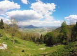 Val di Susa, beautiful view of the green valley with people standing on the grass from Sacra di San Michele, Torino, Italy
