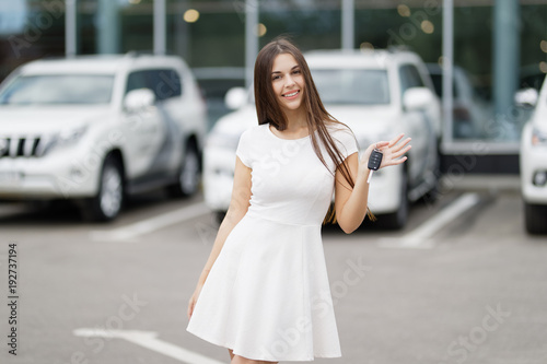 Poster Happy woman driver showing car keys