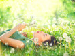 Leinwanddruck Bild - Beautiful young woman lying on green grass and blowing dandelions. Allergy free concept