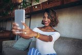 Happy black woman using digital tablets while sitting in modern cafe, make selfie photo - 192746370