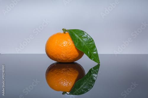 Orange mandarine mit grünem Blatt - citrus Frucht
