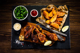 Grilled drumsticks with baked potatoes on wooden background - 192749701