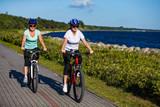 Women riding bicycles at seaside - 192749787