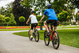 Healthy lifestyle - people riding bicycles in city park - 192749963