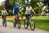 Healthy lifestyle - people riding bicycles in city park - 192749972