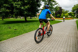 Healthy lifestyle - people riding bicycles in city park - 192749979