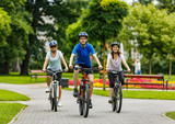 Healthy lifestyle - people riding bicycles in city park - 192749990