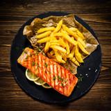 Fried salmon with french fries on wooden table - 192750112