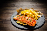 Fried salmon with french fries on wooden table - 192750122