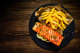 Fried salmon with french fries on wooden table - 192750133