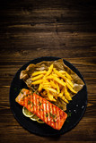 Fried salmon with french fries on wooden table - 192750142