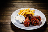 Barbecued drumstick with french fries on wooden table - 192750916