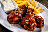 Barbecued drumstick with french fries on wooden table - 192750919