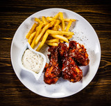 Barbecued drumstick with french fries on wooden table - 192750928