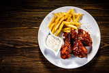 Barbecued drumstick with french fries on wooden table - 192750939