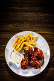 Barbecued drumstick with french fries on wooden table - 192750958