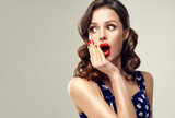 Surprised and amazed girl holds  her cheeks and looks in the side .  Beautiful woman with curly hair and red nails. Expressive facial expressions.  Presenting your product.   - 192754906