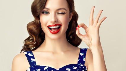 Pin-up retro girl with curly hair  winking, smiling and showing OK sign . Presenting your product. Expressive facial expressions © Sofia Zhuravetc