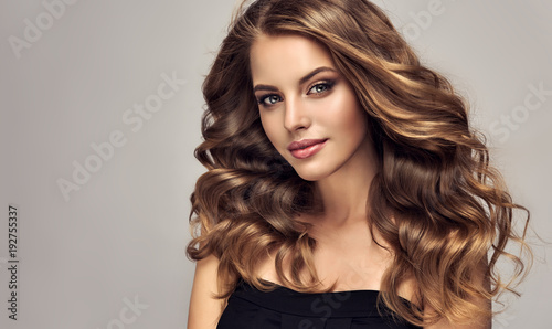 Leinwandbild Motiv Brunette girl with long and shiny wavy hair . Beautiful model with curly hairstyle .