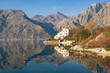 Mountains and coast with white building are reflected in the water. Montenegro, Bay of Kotor, Dobrota town, winter