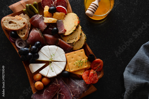 cheese-plate-on-a-board-a-different-cheese-with-meat-snack-jamon-prosciutto-camembert-parmesan-olive-basiron-pesto-with-basil-tapas-bar-top-view
