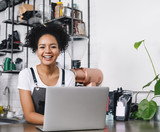 Happy business owner standing at counter with her laptop - 192760514