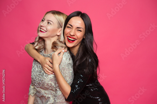 Leinwandbild Motiv Friends forever. Close up photo of Two happy young beautiful smiling girlfriends in little black dresses posing and having fun on a pink background.