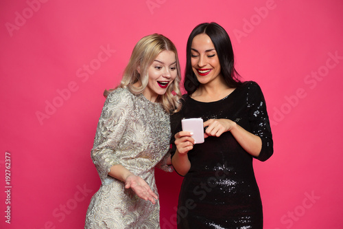 Leinwandbild Motiv Rest with phones. Two stylish smiling beautiful women in evening dresses write messages on the phone or use the Internet on a pink background.