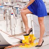 Woman standing one leg on marina bitt - 192765109