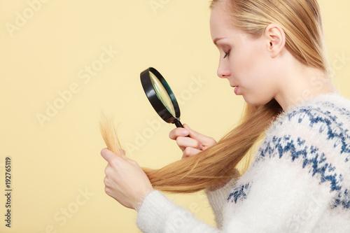 Foto op Canvas Kapsalon Sad woman looking at damaged hair ends.