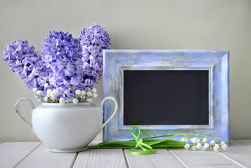 Blue springtime background. Blue hyacinth and lily of the valley flowers around blackboard in blue frame, space