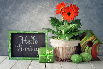 Blackboard with Spring decorations: orange gerberas, lily of the valley, birdhouse and painted Easter eggs, text