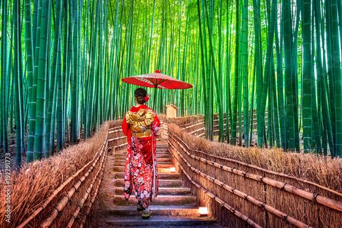 Leinwandbild Motiv Bamboo Forest. Asian woman wearing japanese traditional kimono at Bamboo Forest in Kyoto, Japan.