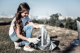 Young volunteer. Cheerful positive young girl holding a glass bottle and putting it into the bag while cleaning garbage - 192792787